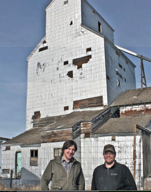 Two men standing in front of grain elevator.