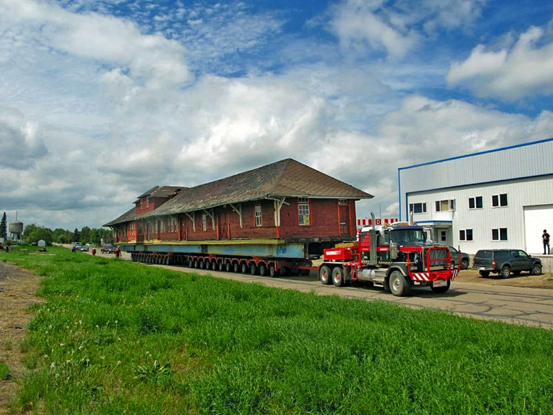 Historical train station being moved on a flatbed trailer