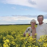 farm couple standing in canola field