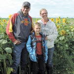 Roger, son Caleb, and Bonita Bott pose in front of their field of sunflowers in Clearwater County.