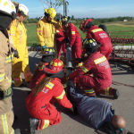 In this training simulation, emergency responders first cut open a portion of a grain auger to assess how badly the 'victim' is injured and then cut the auger to free its leg.