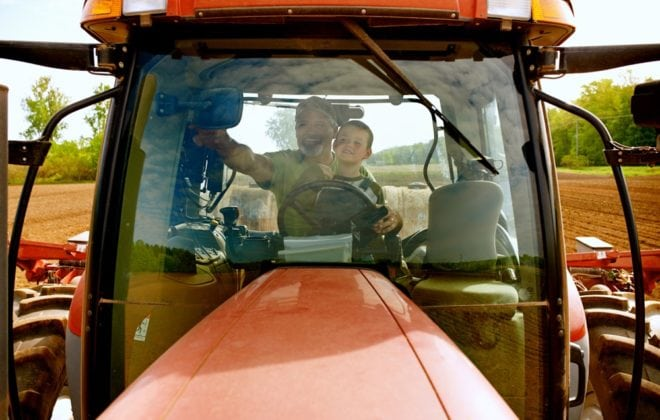 Shot of a young boy sitting with his dad inside the cab of a modern tractor