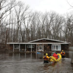 Officials check on a flooded home in the Constance Bay area in Ottawa on April 26. A grant of nearly $250,000 from the Intact Foundation for a quartet of flood mitigation projects was announced as communities in Ontario, Quebec, and New Brunswick were battling devastating floods.