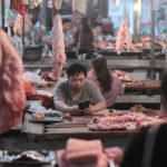 Pork accounts for nearly two-thirds of China's meat consumption and with African swine fever decimating Chinese production, Canada's pork sector had hoped to see its exports to China jump rather than be banned. Pictured here are pork vendors at a market in Yunnan province in May.