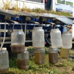 This device, developed by Manitoba Agriculture, compares run-off (collected in the top row of jars) to water that seeps through soil. Management practices can significantly increase the ability of soil to absorb water — but water retention, organic matter, aggregation, soil structure compaction and nutrient cycling are all interconnected, says Farming Smarter researcher Gurbir Dhillon.